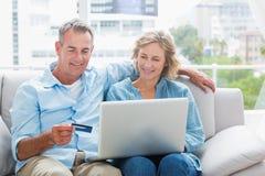 Lächelnde Paare, die auf ihrer Couch unter Verwendung des Laptops sitzen, um an zu kaufen Stockbild