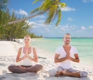 Lächelnde Paare, die auf tropischem Strand meditieren Lizenzfreies Stockfoto