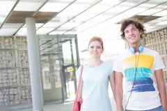 Lächelnde Paare, die bei der Stellung in der Stadt weg schauen Stockbild