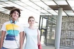 Lächelnde Paare, die bei der Stellung in der Stadt weg schauen Lizenzfreie Stockfotografie