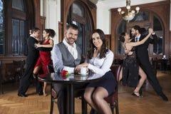 Lächelnde Paare, die bei Tisch während Tänzer durchführen Tango sitzen lizenzfreie stockfotografie