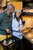 Lächelnde Paare, die Brot kaufen Lizenzfreie Stockfotos