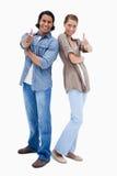 Lächelnde Paare, die Daumen aufgeben Stockbilder