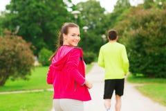 Lächelnde Paare, die draußen laufen Lizenzfreie Stockfotos