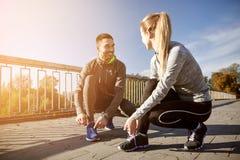 Lächelnde Paare, die draußen Spitzee binden stockfotografie