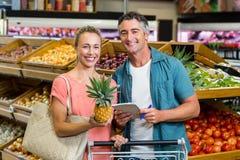 Lächelnde Paare, die eine Ananas und eine Einkaufsliste halten Lizenzfreie Stockfotos