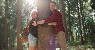 Lächelnde Paare, die einen Baum im Holz umarmen Stockfoto
