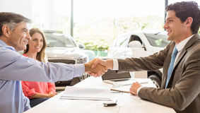 Lächelnde Paare, die einen Neuwagen kaufen lizenzfreie stockfotos
