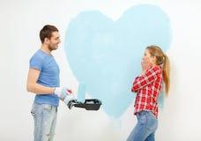 Lächelnde Paare, die großes Herz auf Wand malen Lizenzfreie Stockfotos