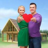Lächelnde Paare, die großes rotes Herz halten Stockbild