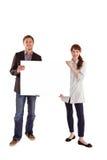 Lächelnde Paare, die großes Zeichen halten Stockfotografie