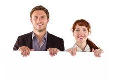 Lächelnde Paare, die großes Zeichen halten Lizenzfreie Stockfotos