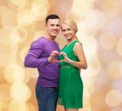 Lächelnde Paare, die Herz mit den Händen zeigen Stockfotos