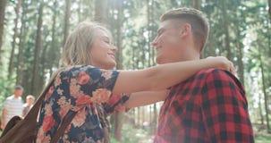 Lächelnde Paare, die im Holz sich umarmen Stockfoto