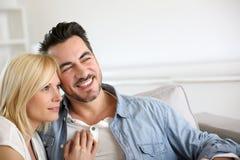 Lächelnde Paare, die im Sofa sich entspannen Stockfoto