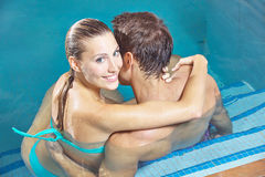 Lächelnde Paare, die im Swimmingpool sitzen lizenzfreie stockbilder