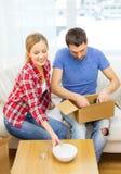 Lächelnde Paare, die Küchengeschirr auspacken lizenzfreie stockfotografie