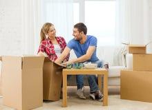 Lächelnde Paare, die Küchengeschirr auspacken stockfotografie
