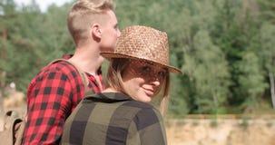 Lächelnde Paare, die Kamera bei der Entspannung im Holz betrachten Stockbild