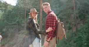 Lächelnde Paare, die Kamera bei der Entspannung im Holz betrachten Stockfotos