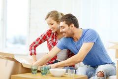 Lächelnde Paare, die kitchenwear auspacken stockfotografie