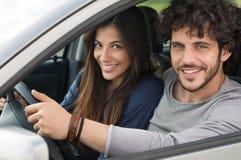 Lächelnde Paare, die mit dem Auto reisen Stockbild