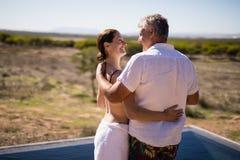 Lächelnde Paare, die nahe Poolside umfassen lizenzfreie stockfotografie