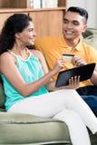 Lächelnde Paare, die online zu Hause kaufen stockfotografie
