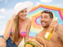 Lächelnde Paare, die Picknick auf dem Strand haben Stockfotografie