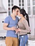 Lächelnde Paare, die rote Rebe im kitchev genießen lizenzfreies stockfoto