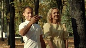 Lächelnde Paare, die selfie im Herbstpark machen lizenzfreies stockfoto