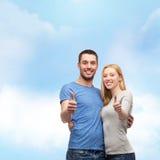 Lächelnde Paare, die sich Daumen zeigen Lizenzfreie Stockfotografie