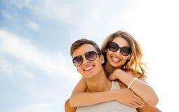Lächelnde Paare, die Spaß über Himmelhintergrund haben Stockfoto