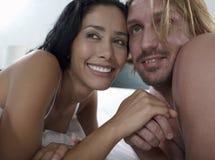 Lächelnde Paare, die weg im Bett schauen stockfoto