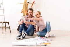 Lächelnde Paare, die Wohnungsplan besprechen Lizenzfreie Stockfotografie
