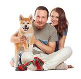 Lächelnde Paare mit dem Hund, der zusammen sitzt lizenzfreie stockfotos
