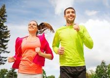 Lächelnde Paare mit den Kopfhörern, die draußen laufen Stockfoto