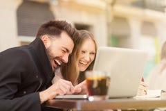 Lächelnde Paare mit einem Laptop lizenzfreie stockfotografie