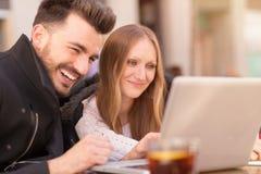 Lächelnde Paare mit einem Laptop stockbilder