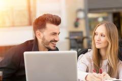 Lächelnde Paare mit einem Laptop stockfotos