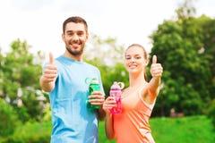 Lächelnde Paare mit Flaschen Wasser draußen Stockbild