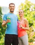 Lächelnde Paare mit Flaschen Wasser draußen Lizenzfreies Stockbild