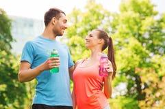 Lächelnde Paare mit Flaschen Wasser draußen Stockfoto