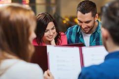 Lächelnde Paare mit Freunden und Menü am Restaurant lizenzfreies stockbild