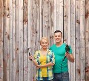 Lächelnde Paare mit Hammer und Bohrgerät lizenzfreies stockfoto