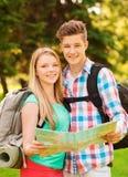 Lächelnde Paare mit Karte und Rucksack im Wald Stockbild