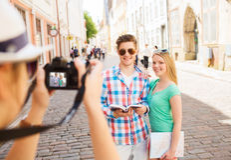 Lächelnde Paare mit Karten- und Fotokamera in der Stadt Stockfoto