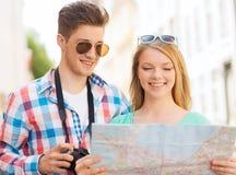 Lächelnde Paare mit Karten- und Fotokamera in der Stadt Lizenzfreies Stockbild