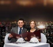 Lächelnde Paare mit Menüs am Restaurant Stockbilder