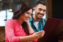 Lächelnde Paare mit Menüs am Restaurant Stockfotos